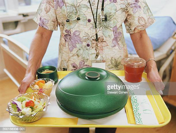 Nurse in hospital room  carrying tray of food, mid section