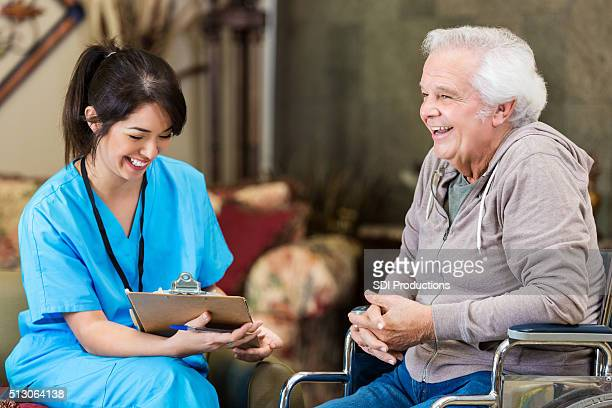 Nurse laughs with senior patient during home visit