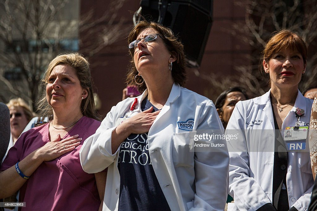 Nurse Lauren Harney (C) places her hand over her chest during a singing of 'God Bless America' during a flag raising ceremony at Boston Medical Center to commemorate the one year anniversary of the Boston marathon bombings on April 14, 2014 in Boston, Massachusetts. Last year, two pressure cooker bombs killed three and injured an estimated 264 others during the Boston marathon, on April 15, 2013.