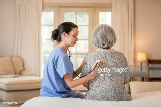 Nurse listening to chest of patient in home