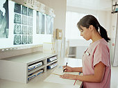 Nurse looking at paperwork in x-ray examination room
