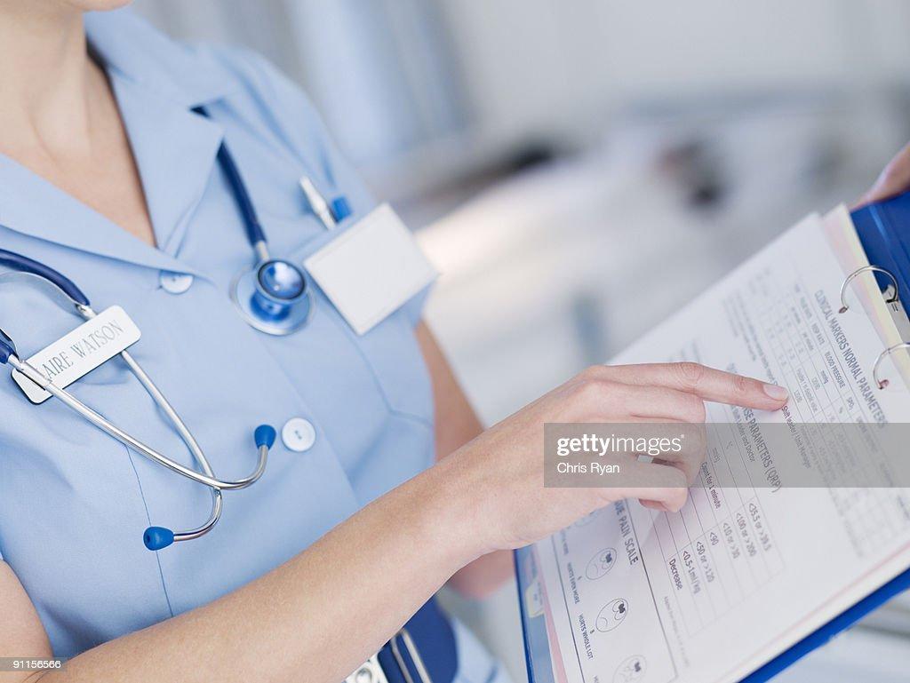 Nurse looking at patientÕs medical chart : Stock Photo