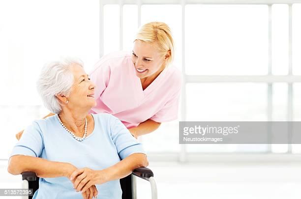 Nurse Looking At Senior Woman While Pushing Wheelchair