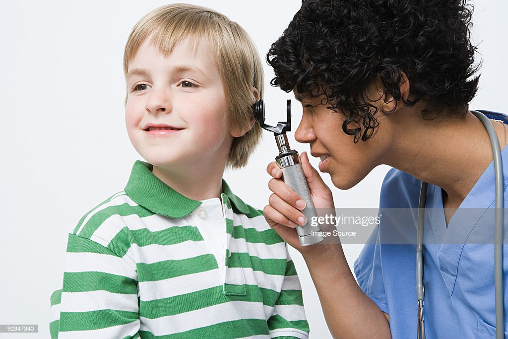Nurse looking in boys ear : Stock Photo
