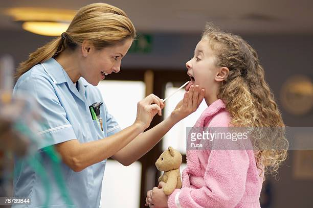 Nurse Looking into Young Girl s Mouth