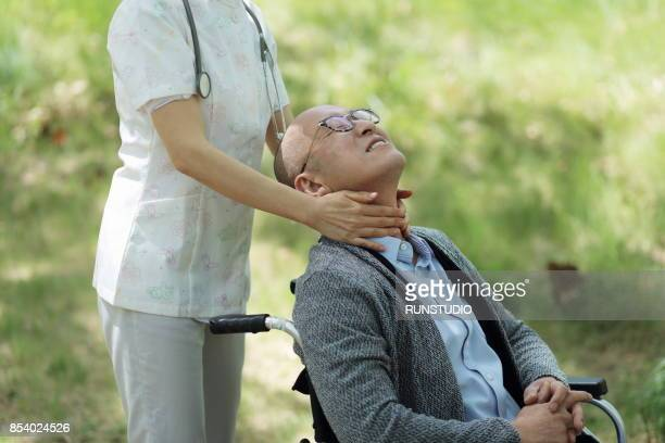 Nurse massaging the neck of senior patient