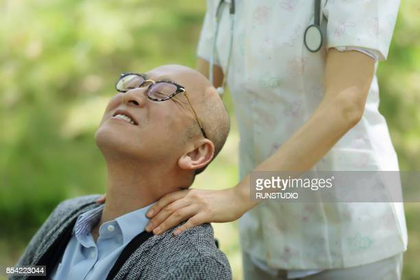 Nurse massaging the shoulder of senior patient