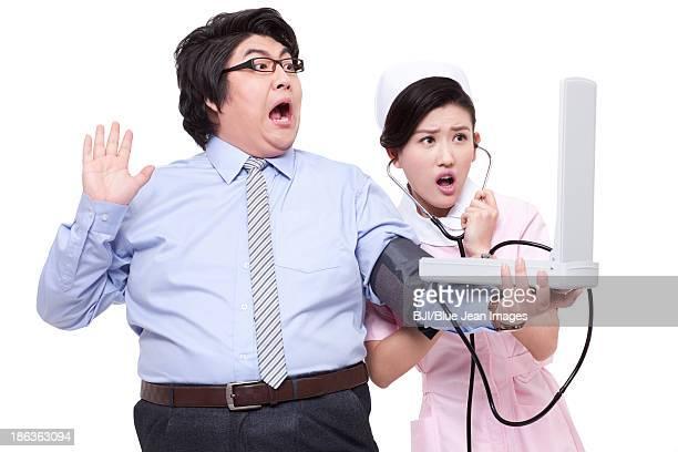 Nurse measuring blood pressure for overweight businessman