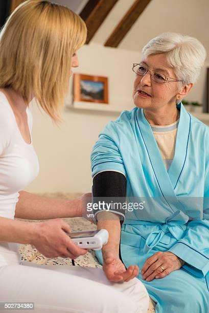 Infirmière mesure la tension artérielle senior femme