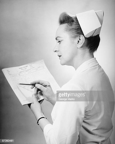 Nurse noting on patient's chart, (B&W)