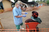 A nurse of the 'Doctors without Borders' medical aid organisation examines a patient in the intake area at a center for victims of the Ebola virus in...