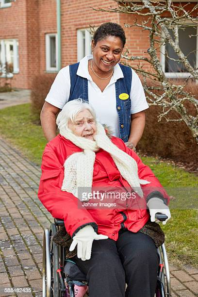 Nurse on walk with senior woman on wheelchair