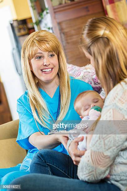 Nurse or lacation consultant talking with new mother and infant