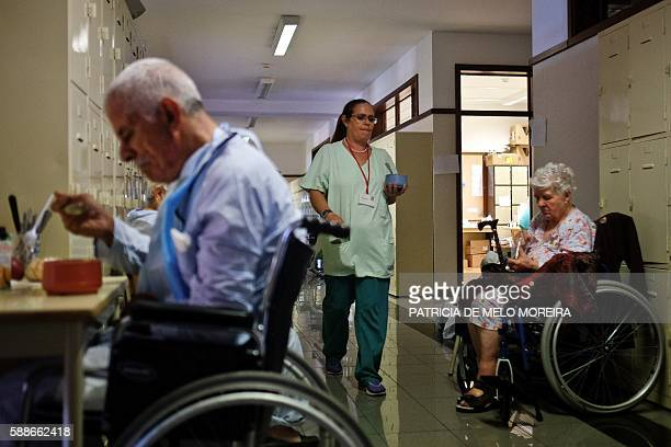 A nurse passes by patients evacuated of the Hospital Joao de Almada that was surrounded by flames during the recent fires at Madeira island as they...