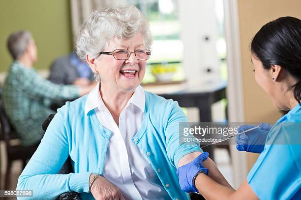Nurse prepares to give senior patient an injection