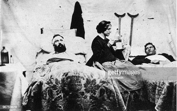 A nurse prepares to spoonfeed soldiers in this photograph taken by Jim Enos inside the Union hospital at Carlisle Barracks Pennsylvania USA circa 1861