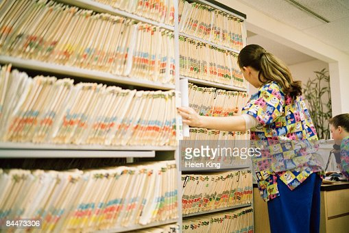 Nurse Pulling Medical Charts From Shelves Stock Photo | Getty Images