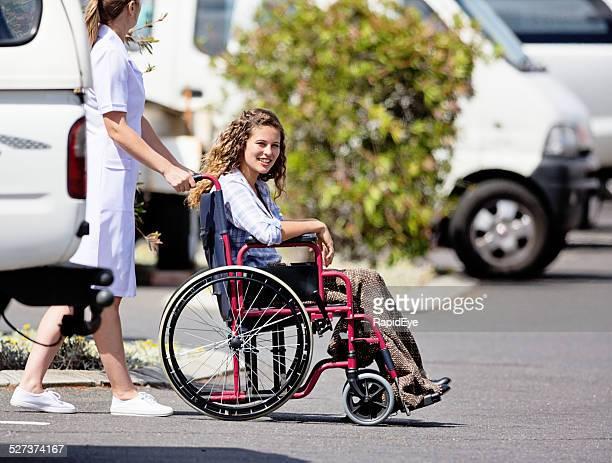 Krankenschwester versucht lächelnde Junge Frau im Rollstuhl an hospital Krankenwagen