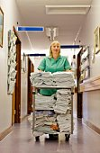 Nurse pushing cart of clean towels and bedding in hallway