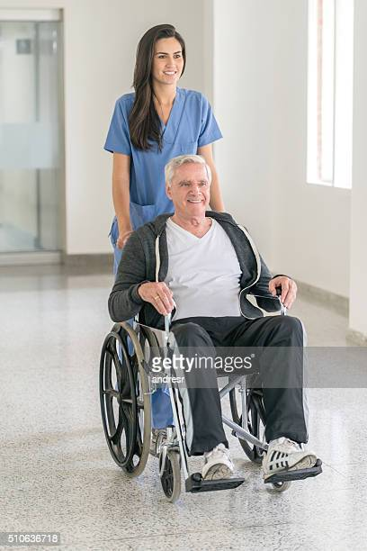Nurse pushing senior male in a wheelchair at the hospital