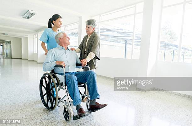 Nurse pushing senior man in a wheelchair at the hospital