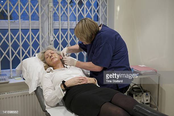 A nurse removes the stitches for a patient a week after her facelift and the surgery to reduce the prominence of her ears The cuts on her eyelids are...