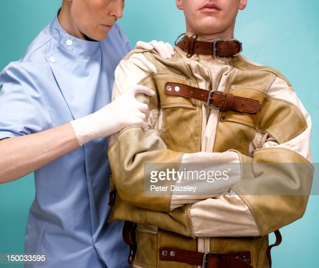 A Nurse Restraining A Man In A Straight Jacket Stock Photo | Getty ...