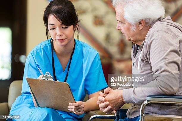 Nurse reveiws patient information with senior man