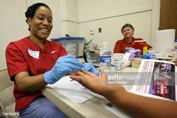 UCLA nurse Rolanda Florence checks the glucose level of a man as nurses and physicians give free basic health screenings and call attention to what...
