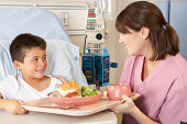 Nurse Serving Child Patient Meal In Hospital Bed