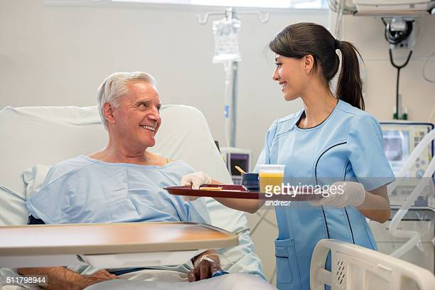 Nurse serving food to patient in the hospital