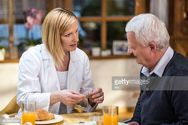 Nurse showing pills to a senior man