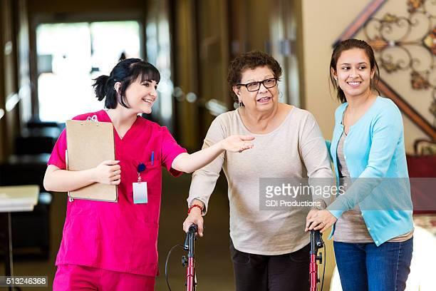 Infirmière montre femme Senior à l'aide de la salle de séjour