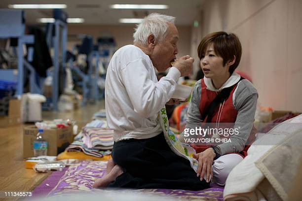 A nurse sits with totally blind tsunami survivor Masakichi Takahashi as he eats relief food at evacuation place as his wife is hospitalized by...