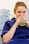 Nurse sitting in chair and holding  coffee cup