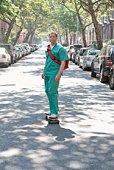 Nurse skateboarding down street