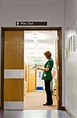 Nurse standing in doorway looking at paperwork