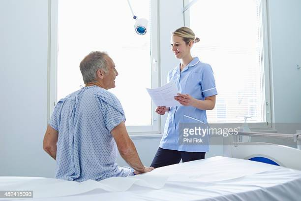 Nurse standing talking to patient sitting on hospital bed
