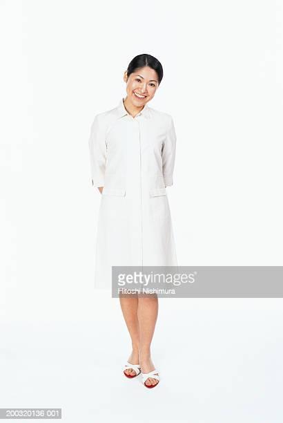 Nurse standing with hands behind back, smiling, portrait