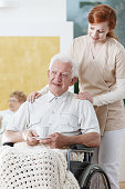 Nurse stands next to disabled older man on wheelchair who holds cup of tea