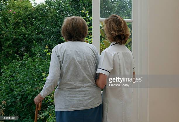 Nurse supporting elderly woman