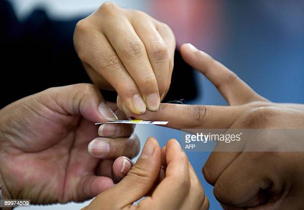 A nurse takes a blood sample to establish the level of cholesterol of a visitor during the World Summit against Obesity in Mexico City on August 20...