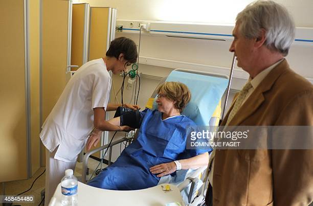 A nurse takes the blood pressure of Annie Claude Gomont suffering from breast cancer as he husband Joel looks on prior to being admitted to the...