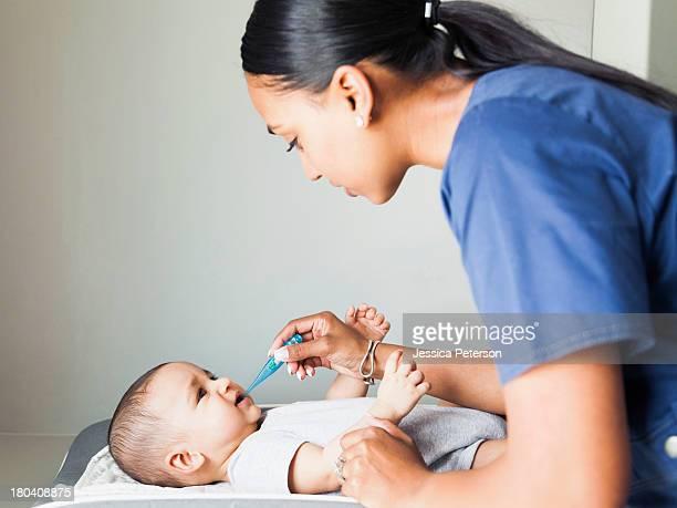 Nurse taking baby boy's (2-5 months) temperature