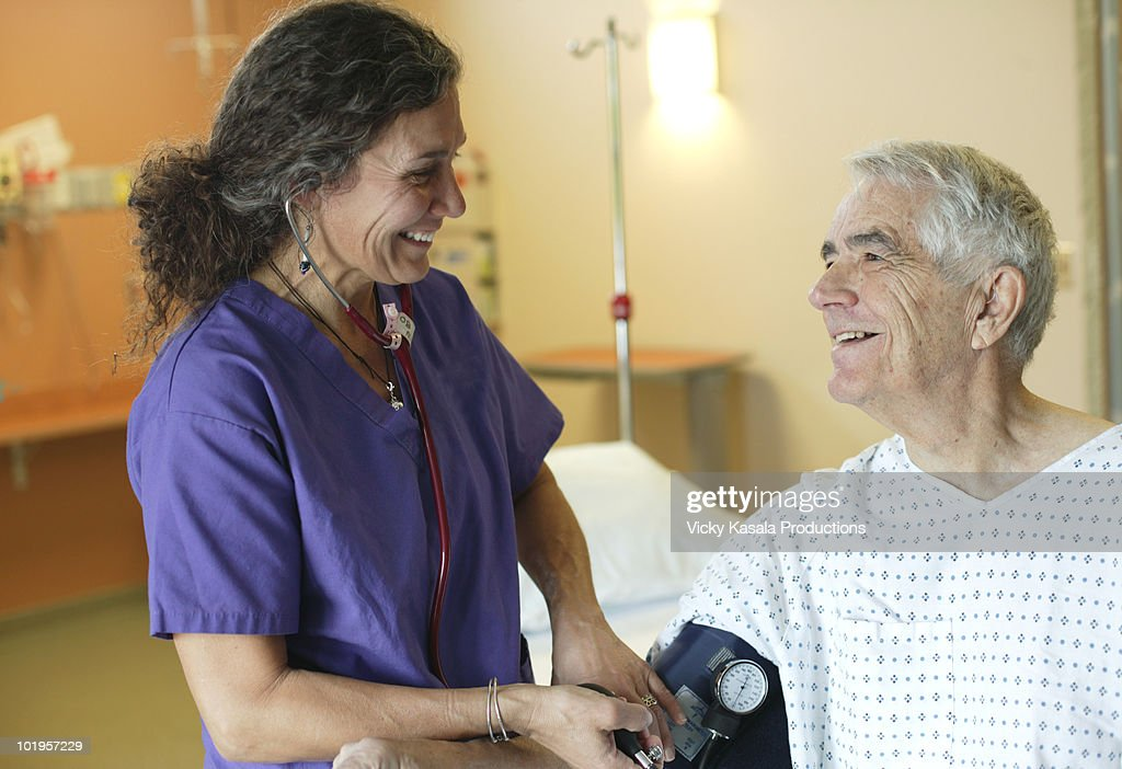 Nurse taking blood pressure of mature man  : Stock Photo