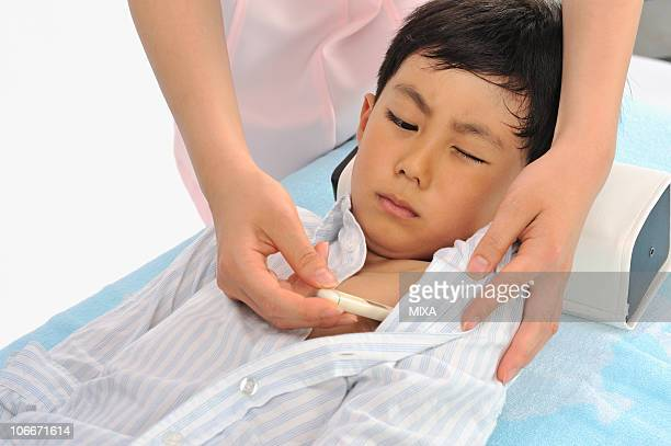 Nurse taking boy's temperature