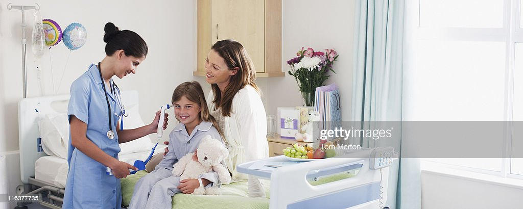 Nurse taking girls temperature with otoscope in hospital : Stock Photo