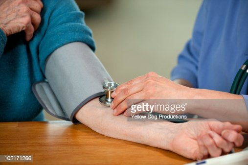 Nurse taking patient's blood pressure : Stock Photo