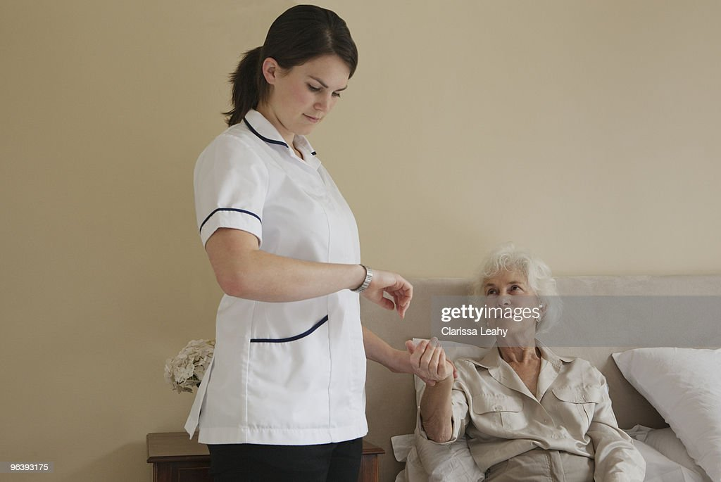 Nurse Taking Pulse Of Elderly Woman Stock Photo | Getty Images