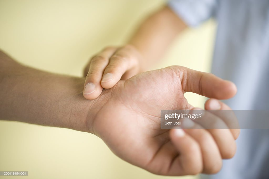 Nurse taking pulse of patient